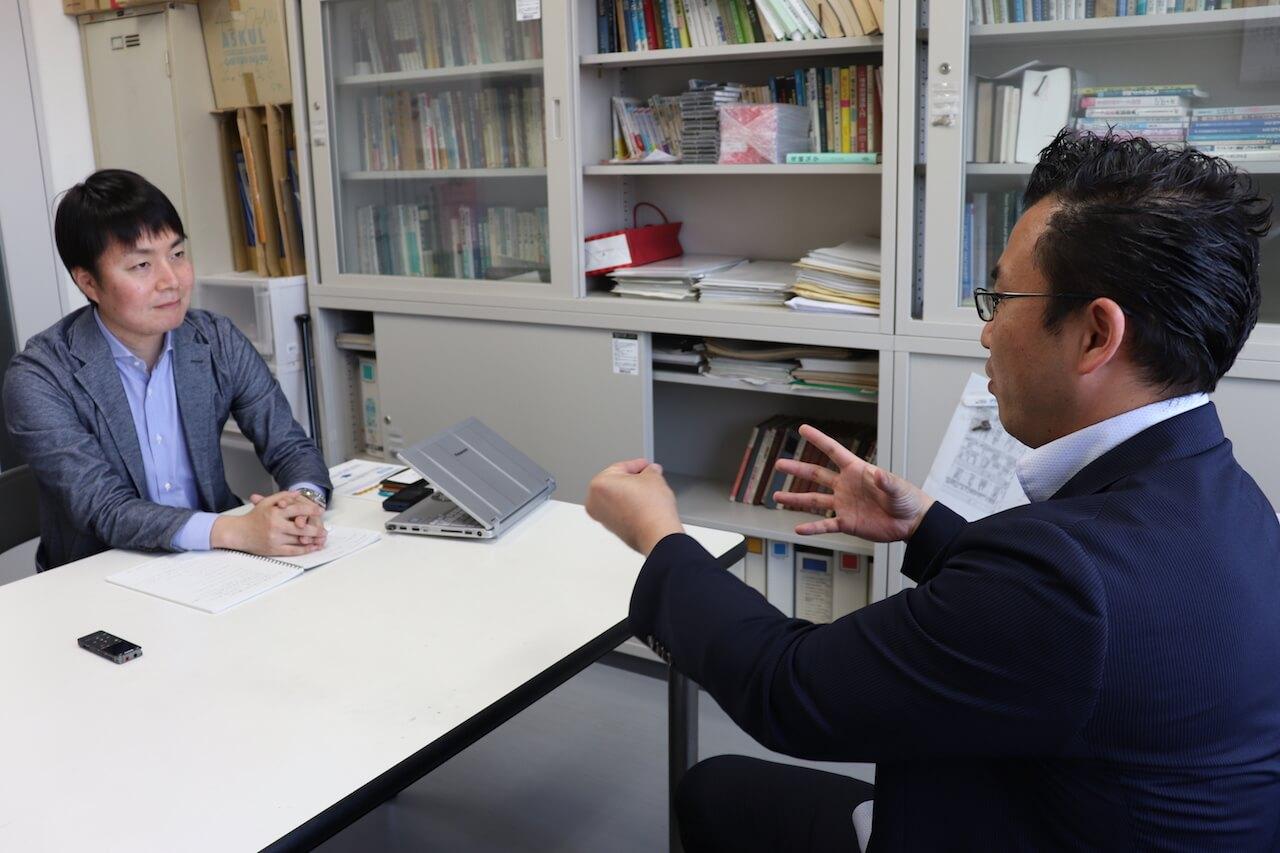 パワーエレクトロニクスについて語る芳賀仁教授(右)とお話を伺うリンカーズ西山(左)